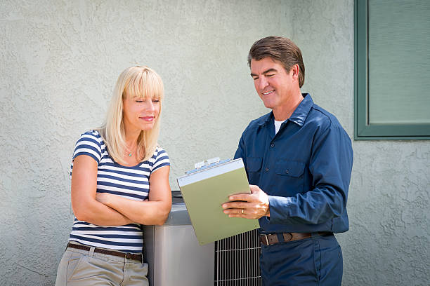 Air Conditioner Repairman Air conditioner repairman in uniform and a clipboard discussing contract with housewife.Take a look at my LIGHTBOXS with other related images. technician stock pictures, royalty-free photos & images