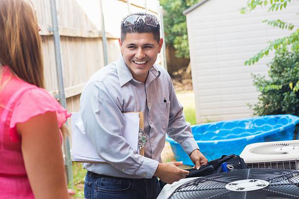 Aire acondicionado reparador hablar con homeowner mientras unidad de inspección - foto de stock
