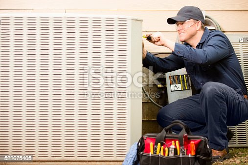istock Air conditioner repairman works on home unit. Blue collar worker. 522675405
