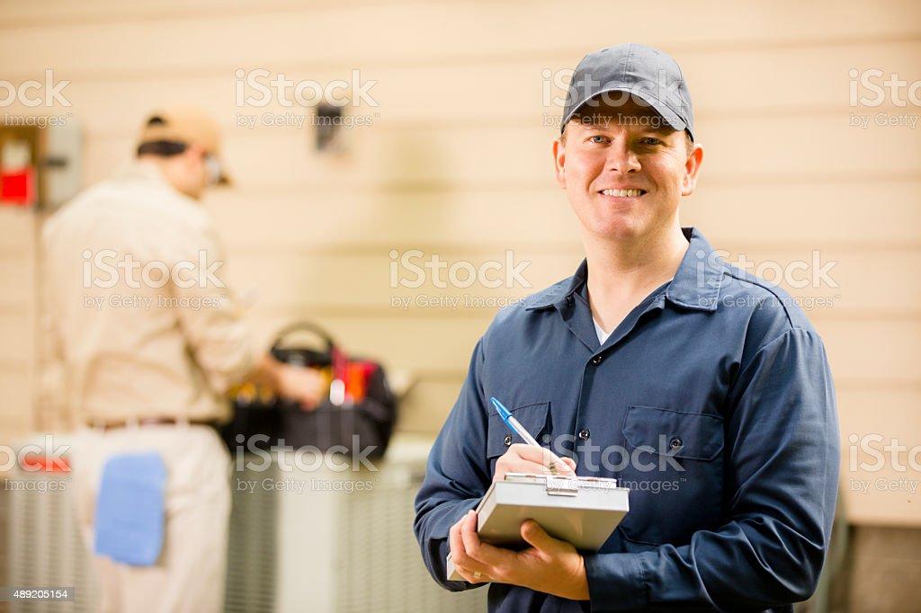 Acondicionador de aire repairmen trabajo en casa unidad. Anillo azul de los trabajadores. - foto de stock