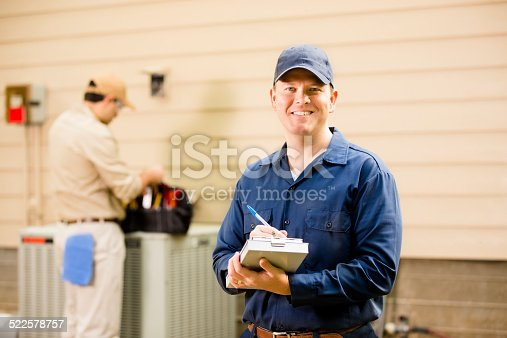 istock Air conditioner repairmen work on home unit. Blue collar workers. 522578757