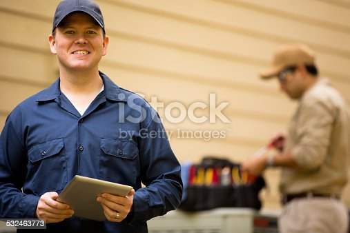 istock Air conditioner repairmen work on home unit. Blue collar workers. 532463773