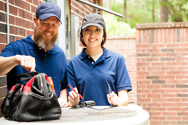 Air conditioner repairmen work on home unit. Multi-ethnic team of one man and one woman repairing a home's air conditioner unit outdoors. They are working on the unit using hand tools in the toolbag.  They wear blue uniforms. technician stock pictures, royalty-free photos & images