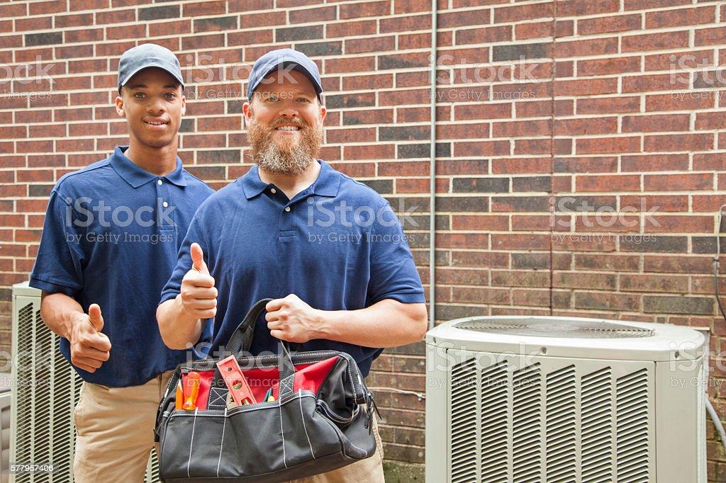 Air conditioner repairmen work on home unit.  Tool bag. stock photo