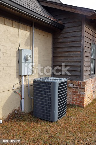Gray Air Conditioner condenser compressor unit next to painted brick house.