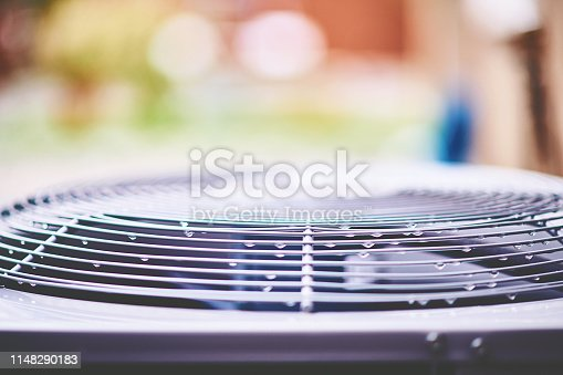 Air conditioner unit with raindrops in residential garden