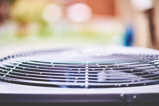 istock Air conditioner unit with raindrops in residential garden 1148290183