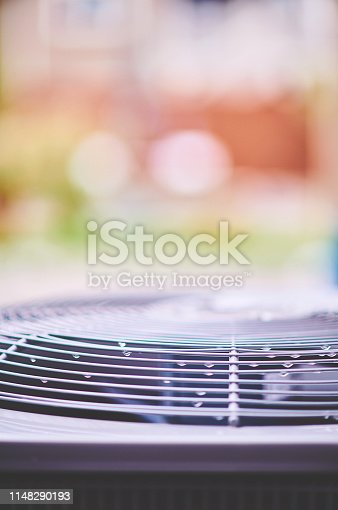 istock Air conditioner unit with raindrops in residential garden 1148290193