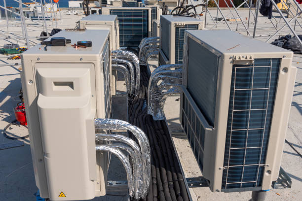 Air conditioner units HVAC on a roof of new industrial building with blue sky and clouds in the background. stock photo