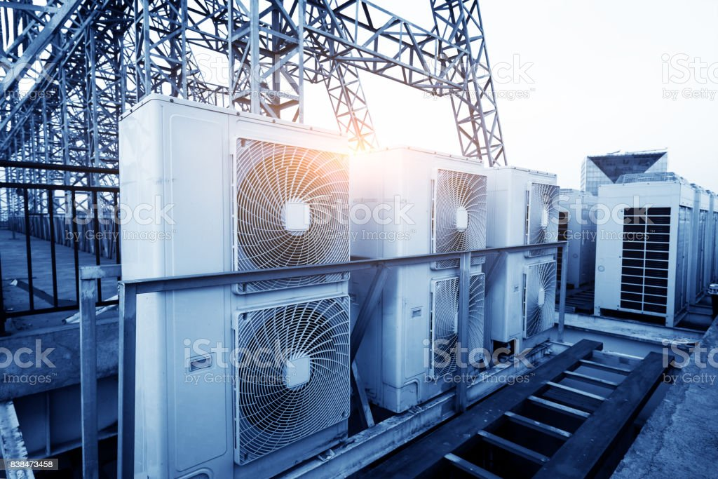 Air conditioner units (HVAC) on a roof of industrial building with blue sky and clouds in the background. stock photo
