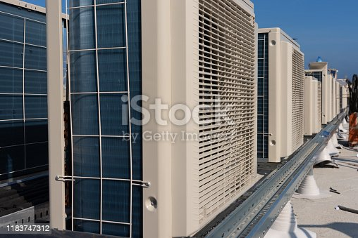 istock Air conditioner units (HVAC) on a roof of new industrial building with blue sky and clouds in the background. 1183747312