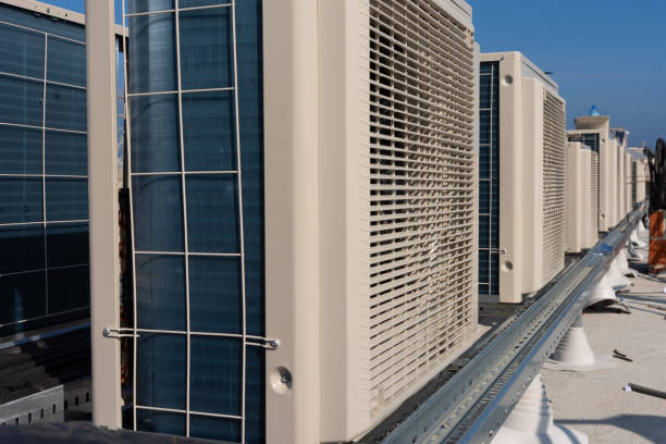 Air conditioner units (HVAC) on a roof of new industrial building with blue sky and clouds in the background. stock photo