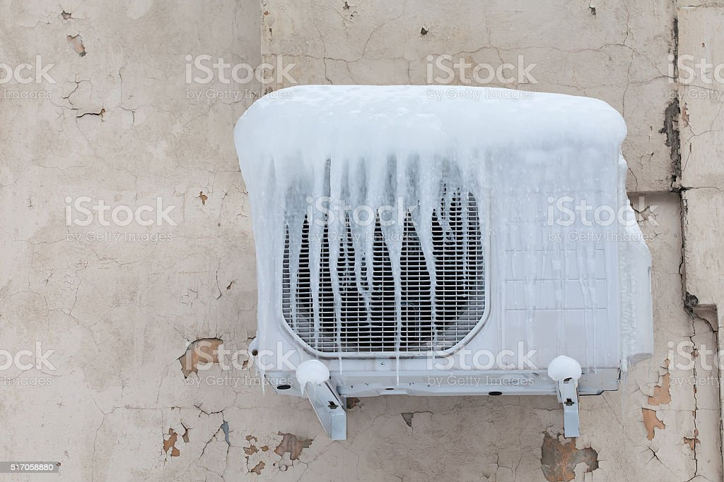 Air conditioner with frozen ice and icicles. Cooling, cold concept stock photo
