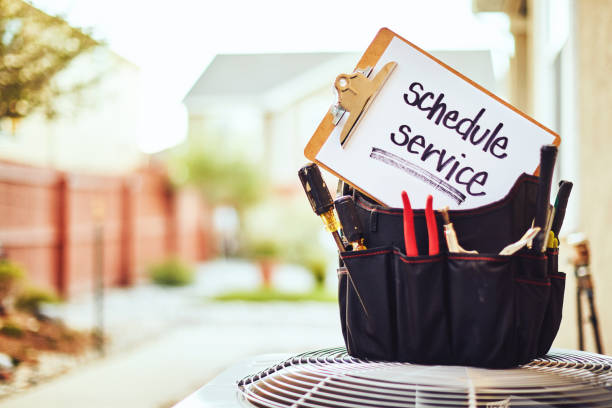 Air conditioner with maintenance tools and service reminder in residential back yard stock photo