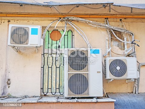 939450782 istock photo Air conditioners hang on the facade of the old house 1222660213
