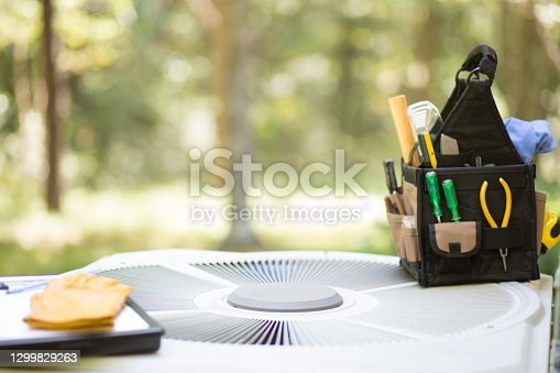 istock Air conditioning service personnel keep home owner unit running efficiently to help save carbon footprint. 1299829263