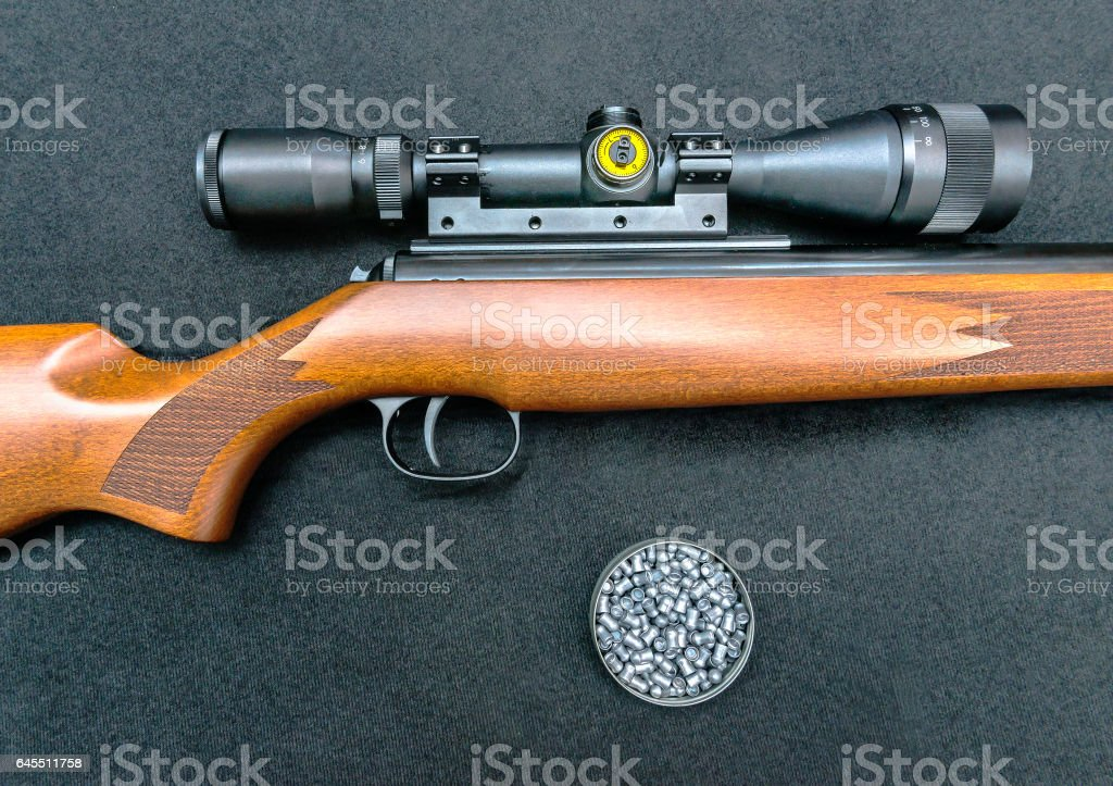 Air gun with wooden butt, scope and pellets on a black background stock photo