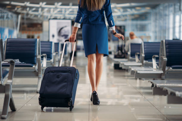 Air hostess going between seat rows in airport Air hostess with suitcase going between seat rows in airport. Stewardess with baggage, flight attendant with hand luggage, aviatransportations job air stewardess stock pictures, royalty-free photos & images