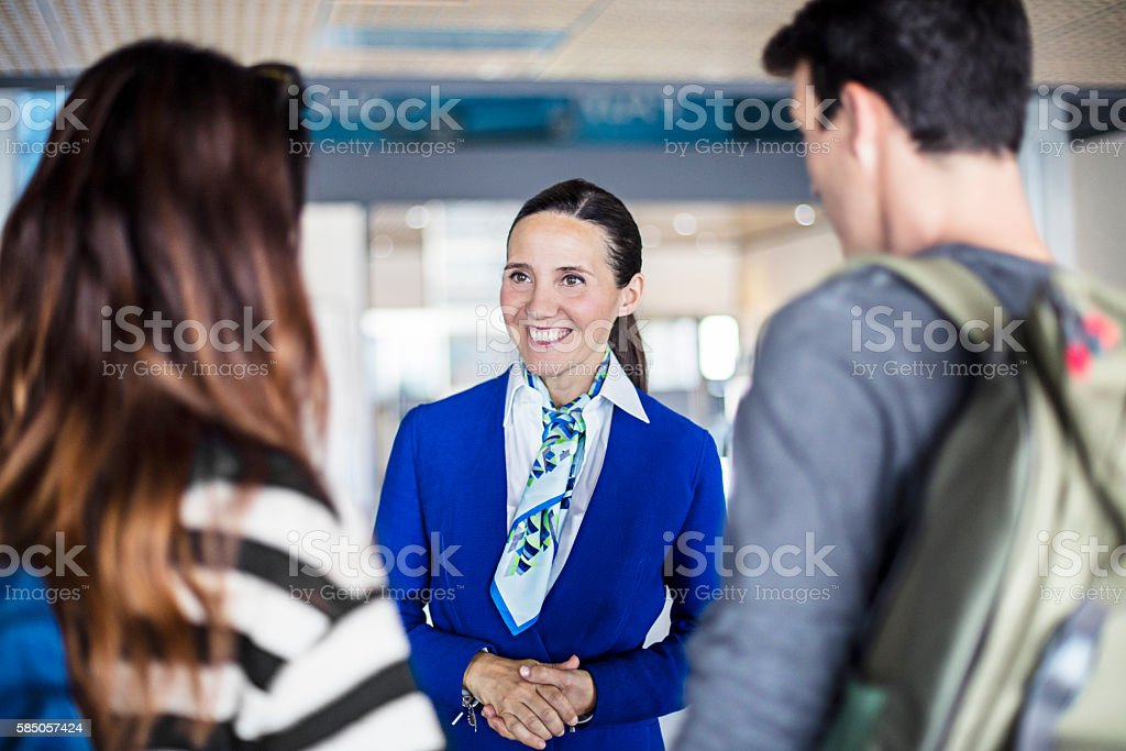 Air hostess helping young couple at airport stock photo