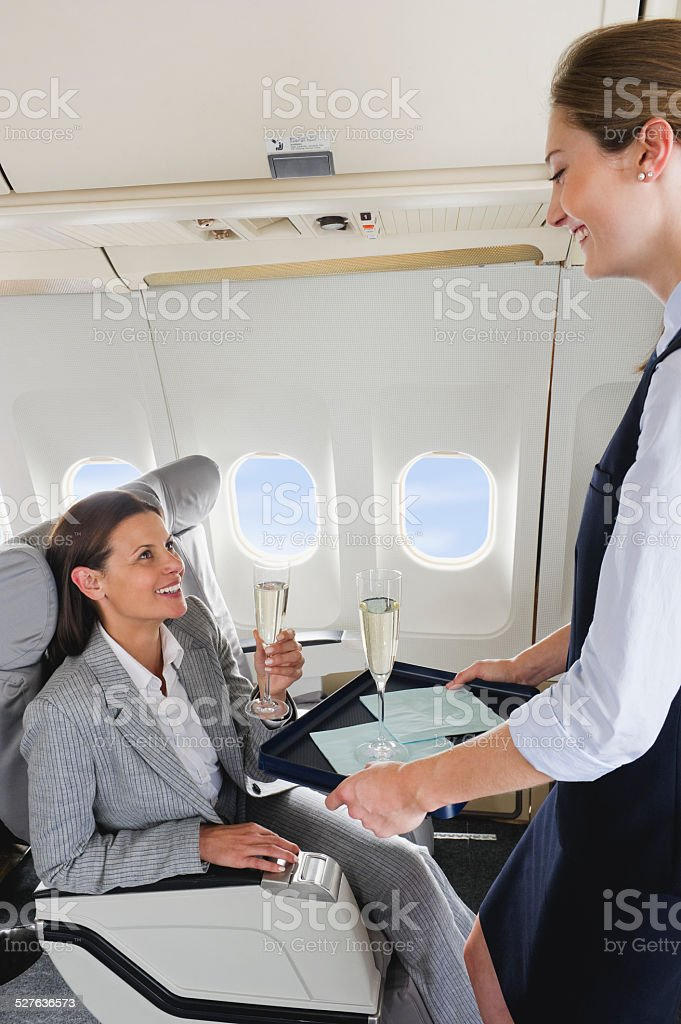 Air hostess serving champagne to businesswoman on airplane stock photo