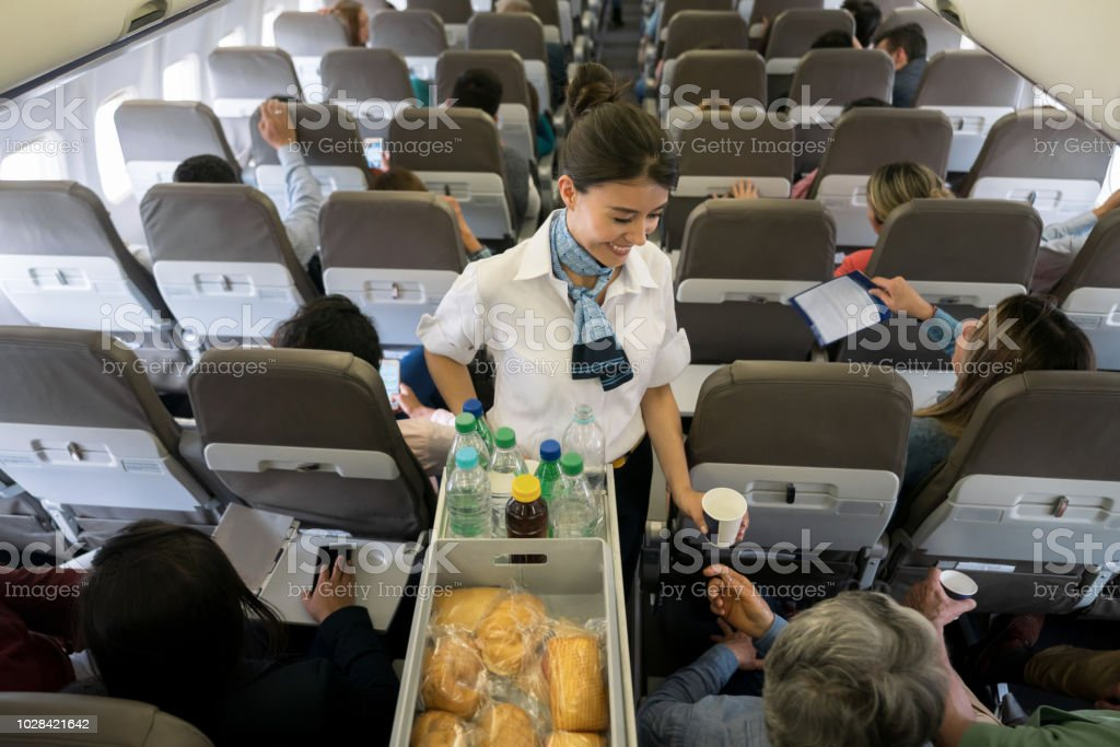 Air hostess serving food and drinks onboard stock photo