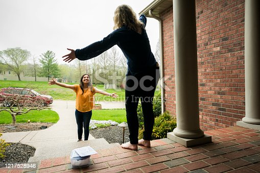 College age 19 year old female best friends give each other air hugs, separated by seven feet,  during the corona virus pandemic practicing social distancing, following orders that prohibit close interaction between people.