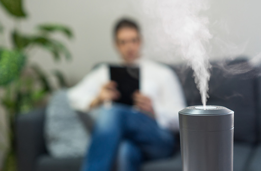 istock Air humidifier at living room. Man using tablet pc on the background. 1131152674