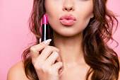 あなたのための空気のキス。ウェーブのかかった髪とは、驚くほど、腕のハード ピンク ポマードの管地豪華なの魅力的な愛らしい女性のクロップ撮影を閉じます。贅沢な唇補正概念
