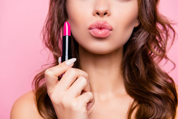 Air kiss for you. Close up cropped shot of femenine gorgeous charming adorable lady with amazing wavy hair do, tube of hard pink pomade in arm. Pampering, lips correction concept stock photo