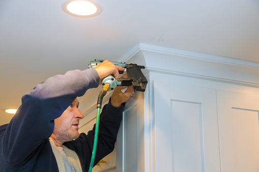 istock Air nailer tool carpenter using nail gun to crown moldings on kitchen cabinets with white cabinets 1185222387