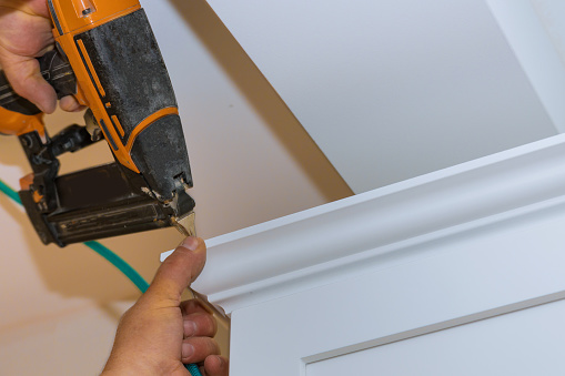 istock Air nailer tool carpenter using nail gun to crown moldings on kitchen cabinets with white cabinets 1191804011