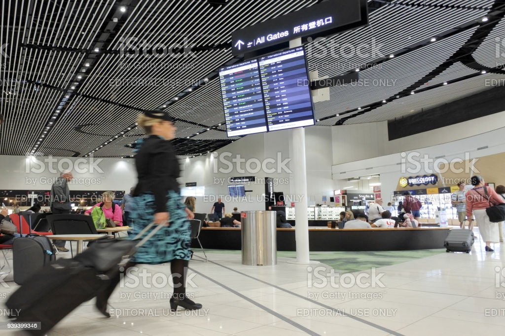 Air New Zealand flight attendant passing through the new Auckland stock photo
