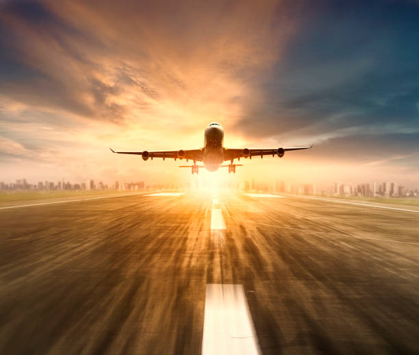 air plane flying over airport runway with city scape and sunset sky background stock photo