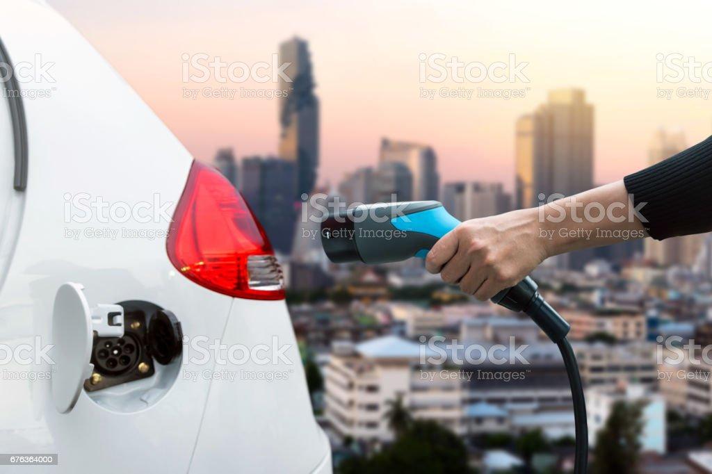 La contaminación del aire y reducir el concepto de las emisiones de gases de efecto invernadero. Mano sosteniendo y carga de vehículos eléctricos con desenfoque de la ciudad Ver antecedentes. foto de stock libre de derechos