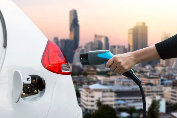 air pollution and reduce greenhouse gas emissions concept. hand holding and charging electric car with blur city view background. - automobile con biodiesel foto e immagini stock