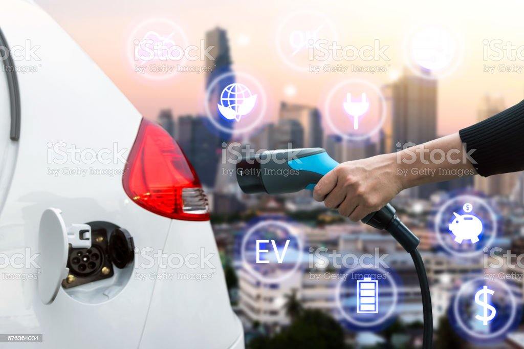 Air pollution and reduce greenhouse gas emissions concept. Hand holding and charging Electric car with blur city view background. - foto stock