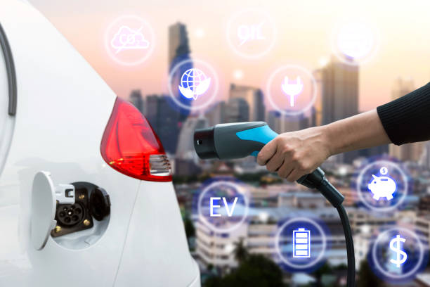 Air pollution and reduce greenhouse gas emissions concept. Hand holding and charging Electric car with blur city view background. stock photo