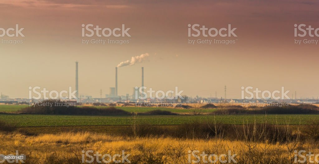 Air pollution from coal-powered plant smoke stacks, and industrial cityscape stock photo