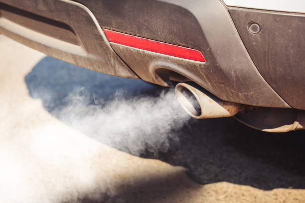 air pollution from dirty and aged vehicle exhaust pipe on road - anidride carbonica foto e immagini stock