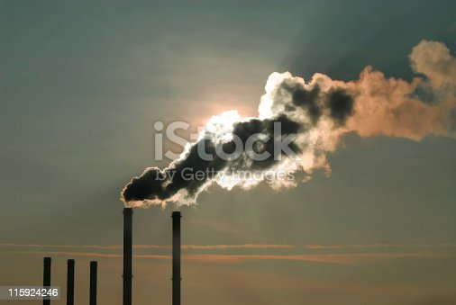 chimney silhouettes - industrial air pollution exhaustion making shadow over sunlight