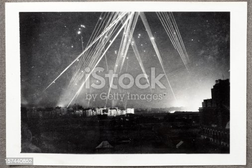 Rare black and white wartime photograph of a night air raid on Alexandria, Egypt in 1943. Anti-aircraft tracer bullets light up the sky and a series of explosions illuminate the right hand horizon. Dust and scratches reflect age and condition of original image.