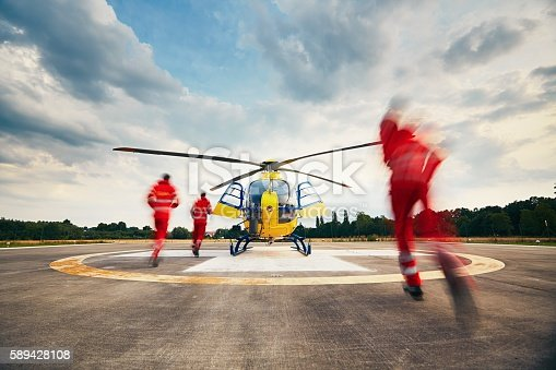 Alarm for the air rescue service. Team of rescuers (paramedic, doctor and pilot) running to the helicopter on the heliport.
