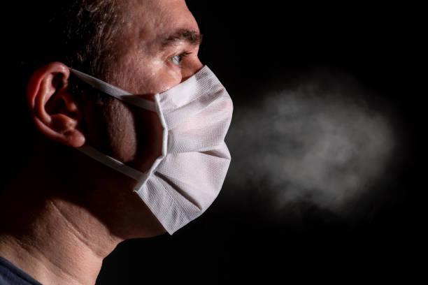 air spread through a cheap defective protective face mask stock photo