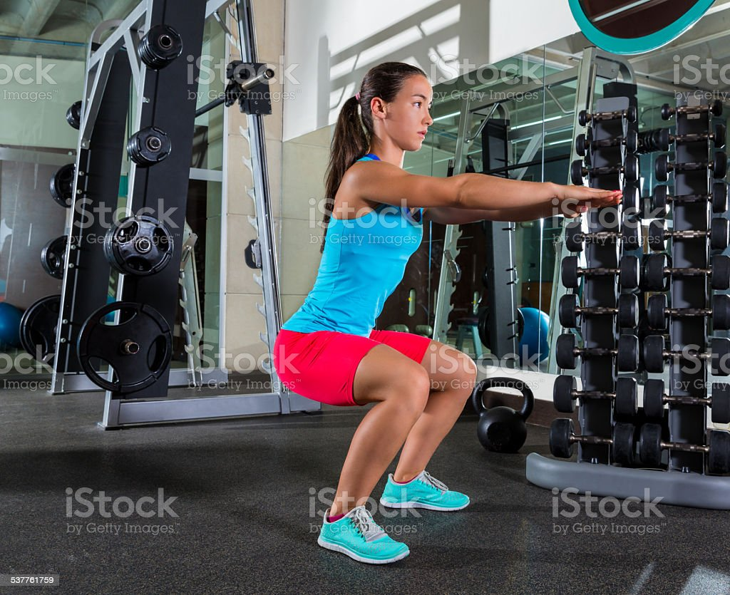 Air squat woman exercise at gym stock photo