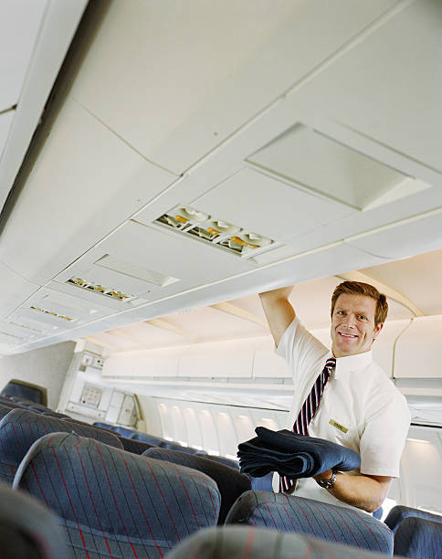 Air steward holding blanket from overhead locker on plane, smiling stock photo