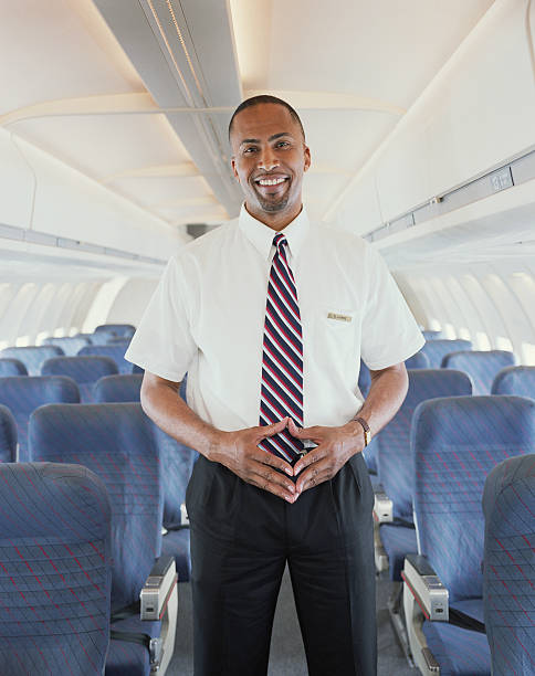 Air steward standing in aisle of aeroplane, smiling, portrait  cabin crew stock pictures, royalty-free photos & images