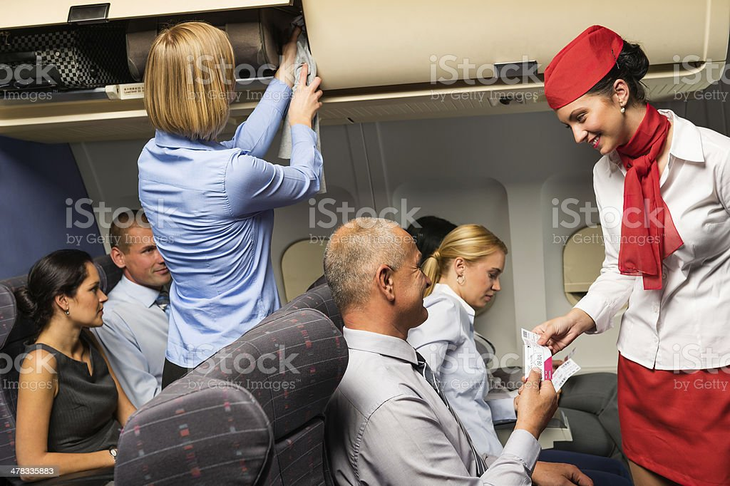 Air stewardess check ticket airplane cabin smiling stock photo