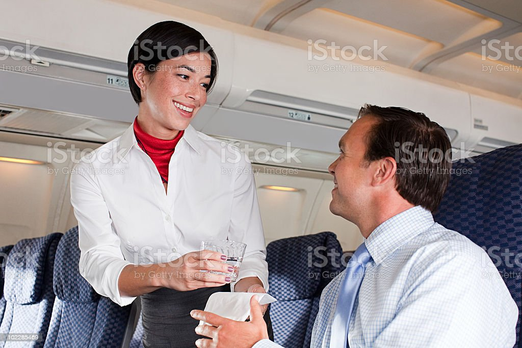 Air stewardess giving drink to passenger stock photo