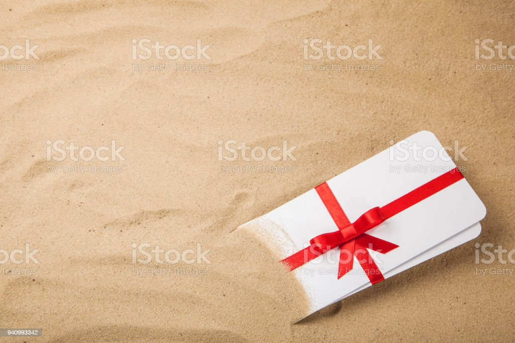Air tickets as a gift with a red ribbon and bow. Background sand...