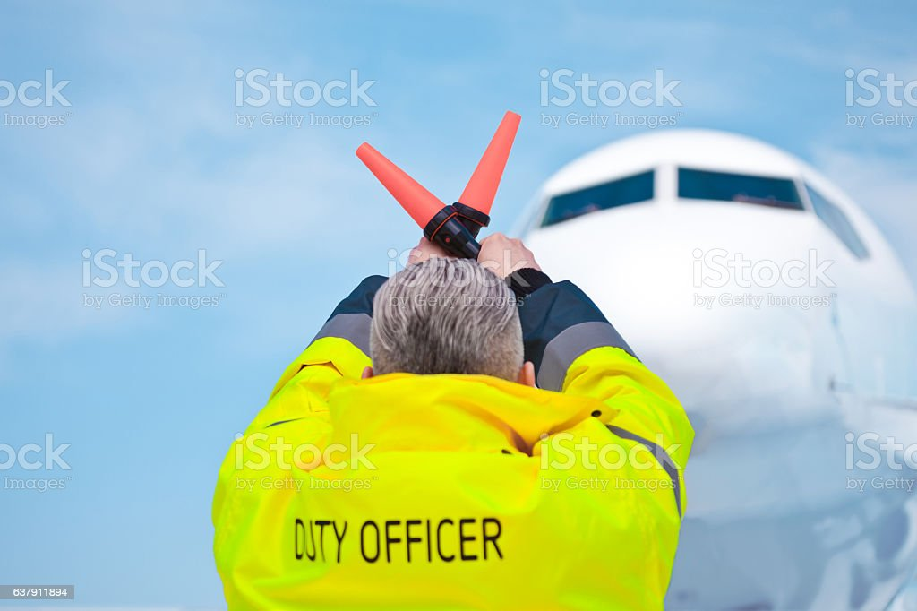 Air traffic controler holding signals Back view of air traffic controler holding signals. Aircraft in the background.  Adult Stock Photo